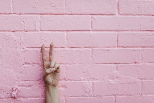 Peace sign on pink wall